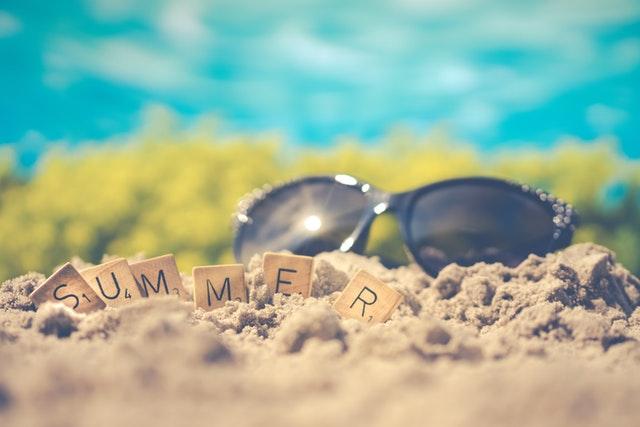 """Slnečné okuliare a nápis """"summer"""" vyskladaný z drevených kociek položené v piesku.jpg"""