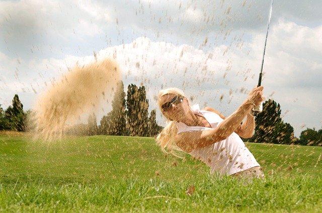 Žena v bielom tričku a slnečných okuliaroch hrá golf.jpg