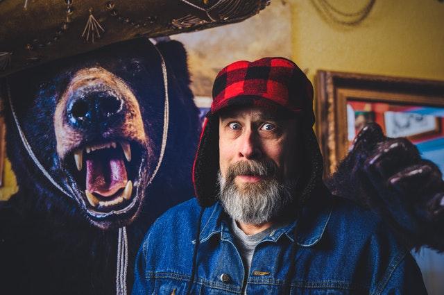 Starší muž s bradou vedľa vypchatého medveďa