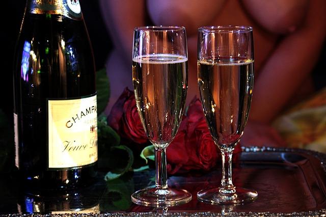 Nahá žena sedí pri pohároch so šampanským